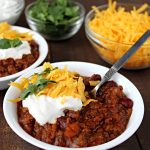 two bowls of beef chili with toppings in smaller bowls.
