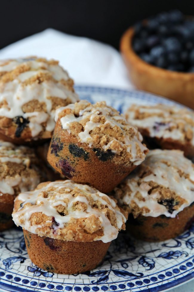 Plate of blueberry muffins with blueberries in a bowl in the background