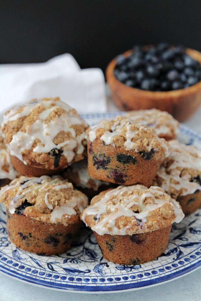 Plate of blueberry muffins with bowl of blueberries in the background.