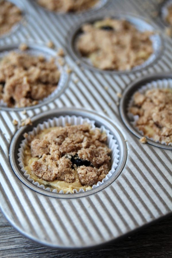 Muffin batter in muffin pan with streusel on top